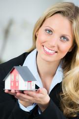 glückliche blonde frau mit miniaturhaus