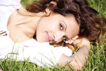 Portrait of beautiful female model laying in the grass