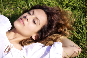 young woman sleeping laying on the grass