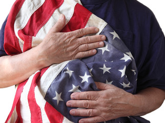 a veteran holds the American flag close to his body