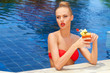 Beautiful blonde in a pool with a cocktail
