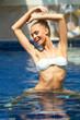 Playful blonde girl looking beautiful in the pool