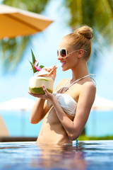 Elegant woman drinking a tropical cocktail