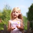 kleines Mädchen spielt draussen mit Blume im Haar