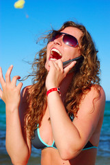 cheerful woman is talking phone near sea