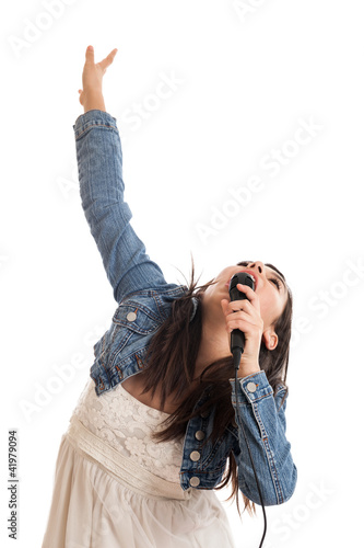 Preteen girl singing with microphone isolated on white