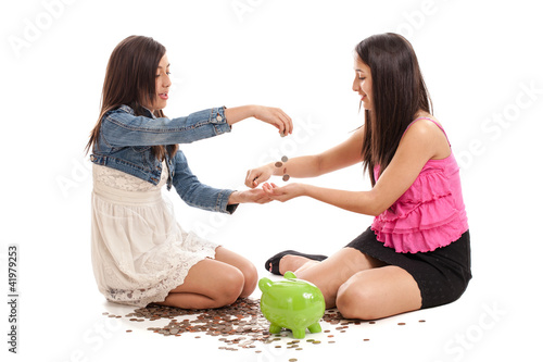 Preteen and teen sisters with piggybank isolated on white
