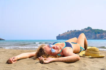 sexy woman is lying on the beach and looking at camera