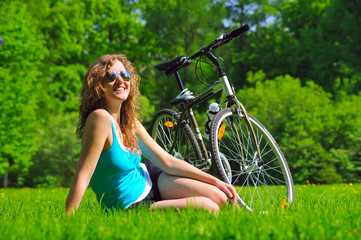 sitting woman near her bike in park