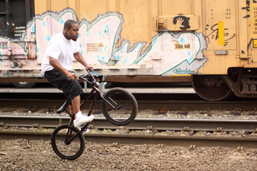 Young black man on a BMX bicycle.