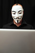 member of Anonymous hacker group at computer