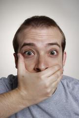 Retrato de un joven sorprendido.Cubriendo la boca.