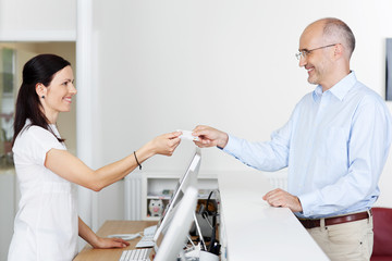 patient überreicht seine karte an der rezeption