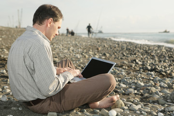 Man with laptop on the beach