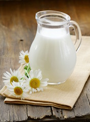 pitcher of milk on a wooden table wish  daisy