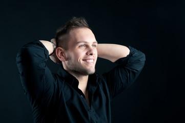 Happy man close up portrait against black background.