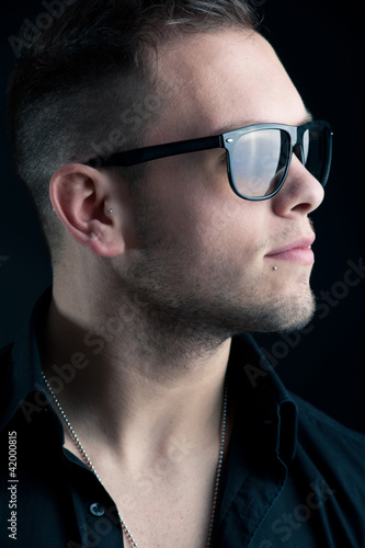 Young boy with sunglasses against black background.