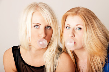 sister posing seriously with bubble gum in mouths