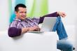 mann sitzt lässig mit dem laptop auf dem sofa