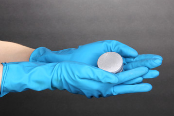 Uranium in hands on grey background