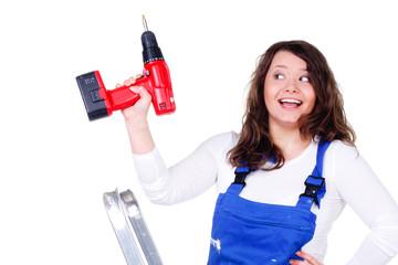 glückliche heimwerkerin hält einen akkuschrauber hoch