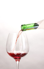 Pouring wine into wineglass isolated on white
