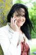 Attraktive lachende Frau im Park beim telefonieren