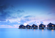 Water villa cottages at sunset on island of Kuredu, Maldives