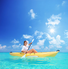 Woman kayaking on a sunny day, Kuredu island, Maldives