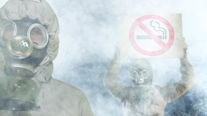 Peples in gas mask holds anti-smoking sign