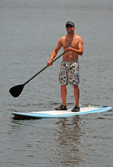 Man getting exercise by paddleboarding