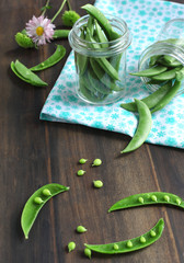 Snow peas pods in jar on a wooden table