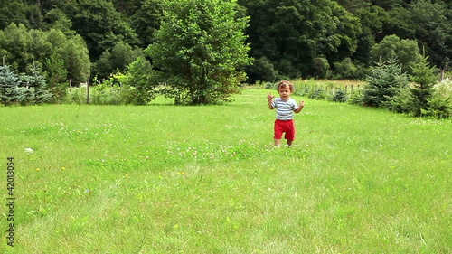 Young baby boy walking on the grass, slow motion