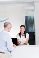 arzthelferin erklärt einem patienten etwas