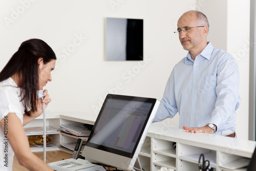 Leinwandbild Motiv arzthelferin schaut im computer