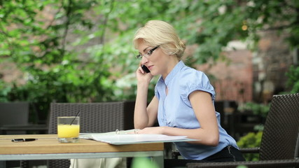 Businesswoman with documents and cellphone in the cafe