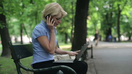 Angry businesswoman with cellphone and laptop in park