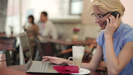 Businesswoman with cellphone and laptop in cafe