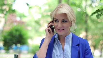 Attractive businesswoman talking on cellphone in the park