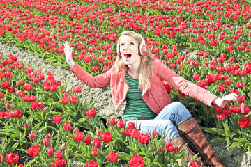 Happy girl enjoying the music in the tulip fields from the Nethe