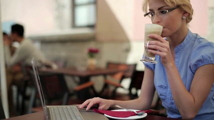 Businesswoman with laptop drinking coffee in cafe