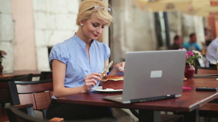 Businesswoman working on laptop and eating lunch in cafe