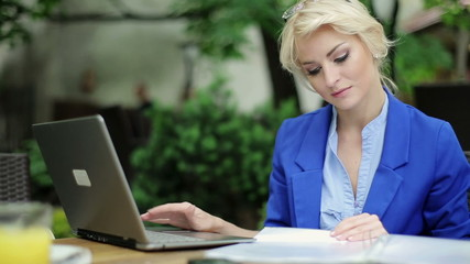 Happy businesswoman with laptop and documents in cafe