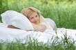 young happy woman relaxing on white bed on natural background