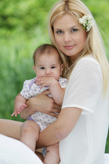 young happy mother and baby on natural background