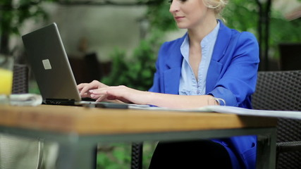 Businesswoman working with laptop and documents in cafe