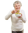 portrait of senior woman eating a fresh salad over white backgro