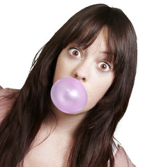 young girl with a pink bubble of chewing gum against a white bac