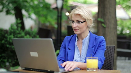 Businesswoman finishing work on laptop and relaxing in cafe