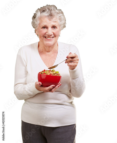 portrait of senior woman holding a cereals bowl against a white